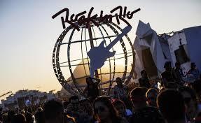 Foto da cidade do rock ao entardecer com o globo e o símbolo do Rock in Rio em contraluz com o pôr do sol