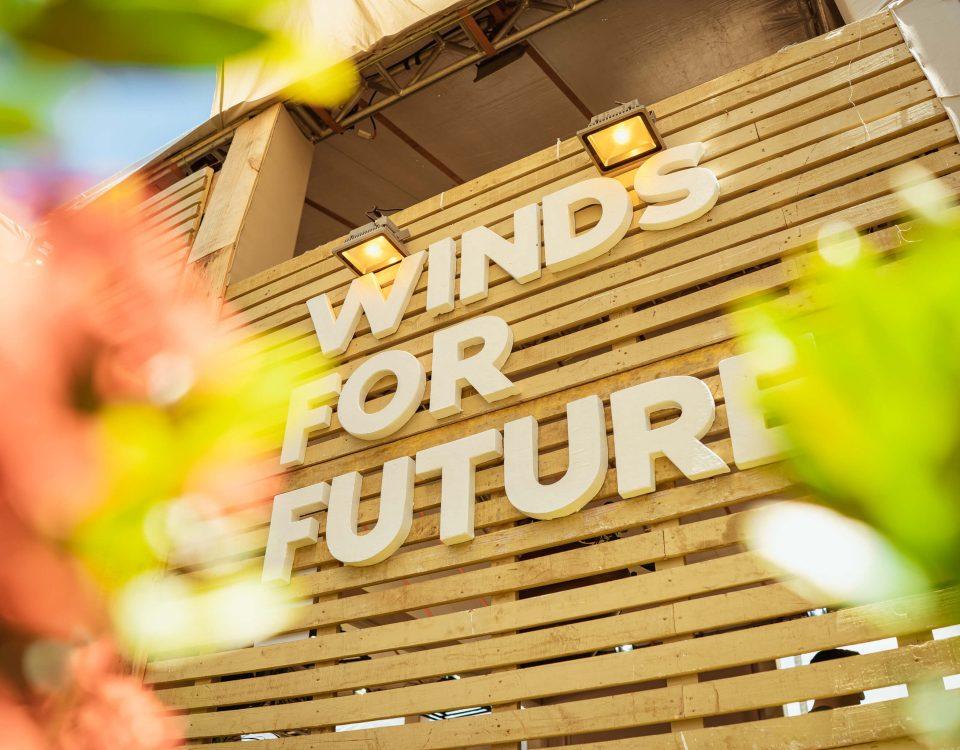 Logotipo da Winds for Future em uma parede de madeira com flores