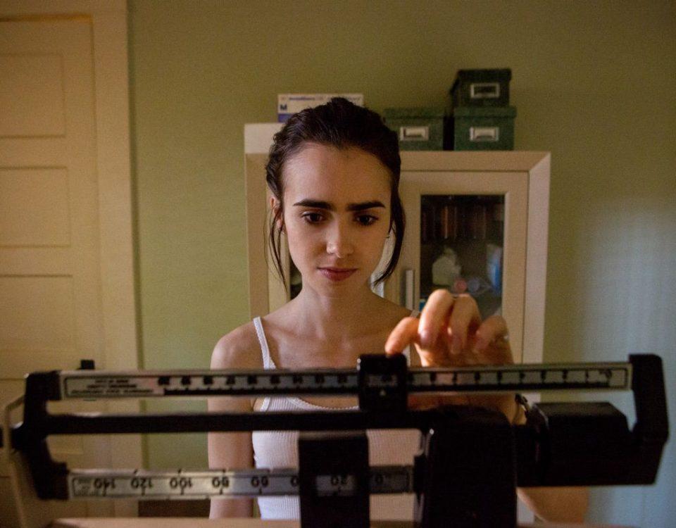 A atriz Lily James se pesando em uma balança em cena do filme O Mínimo Para Viver, sobre saúde mental