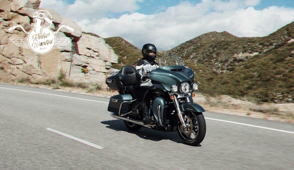 Motociclista pilotando uma moto Harley-Davidson preta em uma estranha rochosa