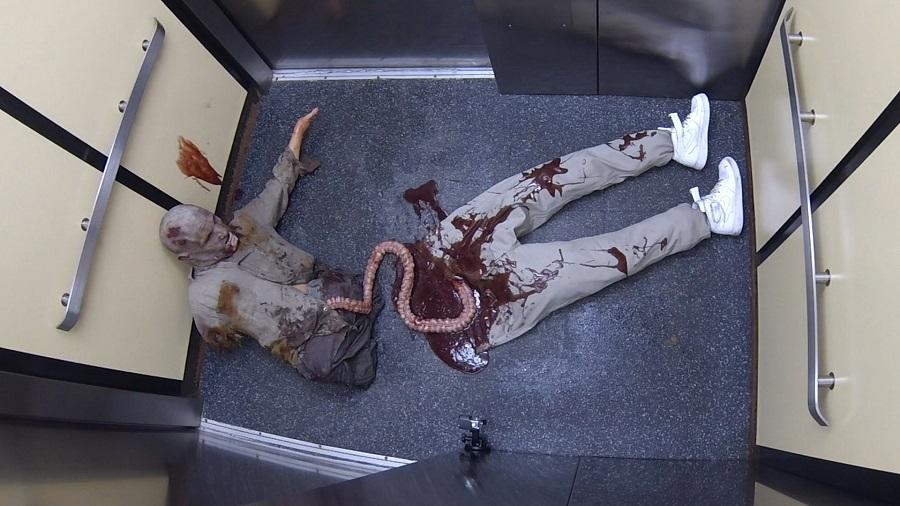 homem vestido de zumbi deitado em um elevador em uma das pegadinhas de terror