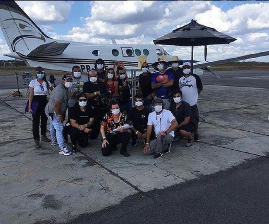 Grupo de elenco e produção de Bem-vinda a Quixeramobim em posando frente a um jatinho, todos usando mãscara