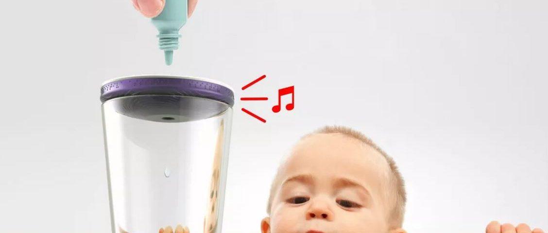 Copo com o conta-gotas sonoro sobre um copo, com alguém segurando um remédio pingando sobre eles e uma sinalização visual que remete a música saindo do dispositivo